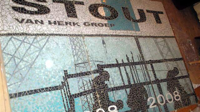 Groot bedrijfslogo en wanddecoratie in mozaiek gemaakt door de medewerkers van de Stout - Van Herk Groep, ontworpen en begeleid door Lieke van Dommelen.