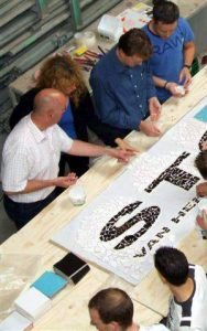 Lieke van Dommelen begeleidt de medewerkers van Sout-Van Herk bij het maken van hun bedrijfslogo in mozaiek.